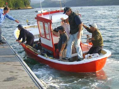 Miguelo,patrón de una de las embarcaciones,con un equipo abordo,atracando en el pantalán.