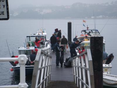 Pescadores y patrones embarcando en el pantalan de Castropol.